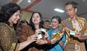Presiden Joko Widodo (kanan) membagi contoh Kartu Indonesia Sehat (KIS) pada Ibu Negara Iriana Widodo (kedua kanan), Menteri Koordinator Pembangunan Manusia dan Kebudayaan Puan Maharani (kedua kiri) dan Menteri Kesehatan Nila F. Moeloek saat peluncuran Kar
