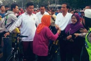 Presiden Jokowi menyapa masyarakat saat bersepeda santai di Sudirman, Jakarta, Minggu (23/11)