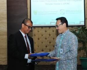 Seskab Andi Wijayanto dan Dirut BPJS Kesehatan Fahmi Idris bertukar dokumen seusai penandatangan kerjasama, di kantor Kemensetneg, Jakarta, Jumat (2/1) sore)