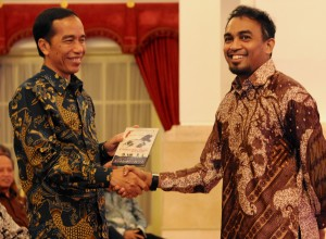 "Presiden Jokowi menerima DVD film ""Cahaya Dari Timur"", dari arti Glenn Fredly, di Istana Negara, Jakarta, Senin (30/3) malam"