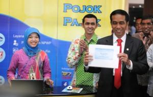 Presiden Jokowi menunjukkan tanda terima setelah menyerahkan SPT Pribadi, di kantor Pusat Dirjen Pajak, Jakarta, Kamis (19/3)