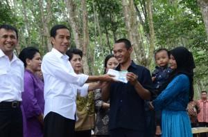 Presiden Jokowi menyerahkan simbolis KIS kepada pekerja PTPN III, di Deli Serdang, Sumut, Sabtu (18/4)