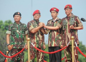 Presiden Jokowi dengan baret dan brevet TNI di antara Panglima TNI dan Kepala Staf TNI, di Lapangan Merah, Mabes TNI Cilangkap, Kamis (16/4)
