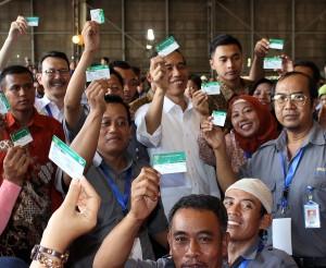 Presiden Jokowi bersama para buruh PT Dok & Perkapalan Bahari menunjukkan KIS, saat, di Cilincing, Jakarta Utara, Selasa (28/4)