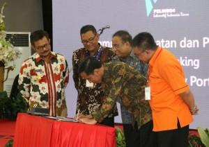 Presiden Jokowi menandatangani sampul groundbreaking MNP disakaikan oleh Menko Kemaritima dan Gubernur Sulsel, di Makassar, Jumat (22/5)