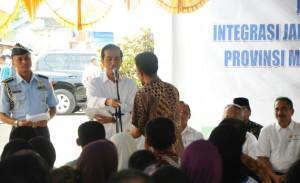 Presiden Jokowi menyerahkan KIS kepada warga saat berkunjung ke Tidore, Maluku Utara, Jumat (8/5)