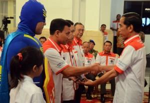 Presiden Jokowi menyerahkan penghargaan kepada tokoh masyarakat yang terlibat dalam pencegahan narkoba, di Istana Negara, Jumat (26/6)