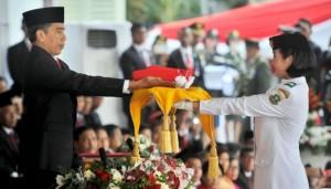 Presiden Jokowi menyerahkan bendera merah putih kepada anggota Paskibraka, pada upacara Peringatan Detik-detik Proklamasi Kemerdekaan RI, di halaman Istana Merdeka, Jakarta, Senin (17/8)