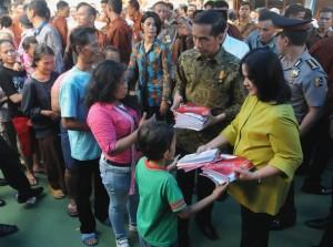 Presiden Jokowi didampingi Ibu Negara Iriana membagikan buku tulis saat blusukan, di Kel. Manggarai, Kec. Tebet, Jakarta Selatan, Kamis (10/9) sore