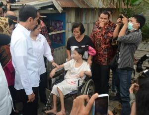 Presiden Jokowi didampingi Menteri Kesehatan Nila F. Moloek berdialog dengan warga, di rumah singgah Seberang Ulu, Palembang, Jumat (30/10)