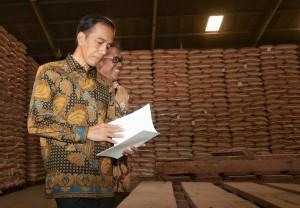 Presiden Jokowi melihat laporan yang diberikan Dirut Bulog saat meninjau Gudang Bulog, di Jakarta Timur, Jumat (2/10)