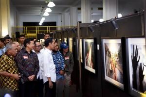 Presiden Jokowi didampingi Dirut Bank Mandiri Budi G. Sadikin dan sejumlah menteri tersenyum menyaksikan pameran foto setahun pemerintahannya, di Museum Bank Mandiri, Jakarta, Jumat (18/12) malam