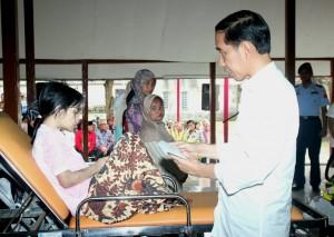Presiden Jokowi menyerahkan kartu ASPDB kepada salah seorang anak yang hadir (17/3). (Foto: Humas/Agung)
