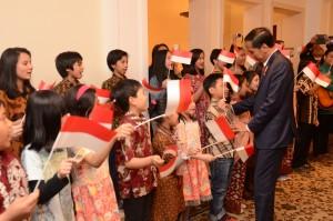 "Sejumlah anak-anak Indonesia menyanyikan lagu ""Berkibarlah Benderaku"" menyambut kedatangan Presiden Jokowi di Berlin, Minggu (17/4) malam waktu setempat. (Foto: Humas/Deni)"