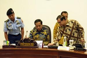 Presiden Jokowi menerima laporan Seskab Pramono Anung sebelum memimpin rapat terbatas, di kantor Kepresidenan, Jakarta, Rabu (13/4) sore. (Foto: Agung/Humas)