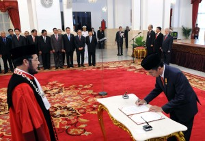 Presiden Jokowi menandatangani berita acara pengambil sumpah Anwar Usman sebagai hakim konstitusi, di Istana Negara, Jakarta, Kamis (7/4) sore. (Foto: JAY/Humas)