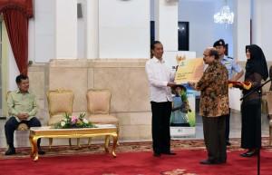 Presiden Jokowi menerima Bukti Setor Zakat dan Kartu Nomor Pokok Wajib Zakat dari Ketua BAZNAS Bambang Sudibyo, Kamis (30/6), di Istana Negara, Jakarta. (Foto: Humas/Jay)
