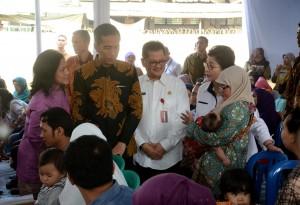 Presiden Jokowi didampingi Ibu Negara Iriana berbincang dengan seorang ibu yang anaknya mengikuti vaksinasi ulang, di RSU Ciracas, Jaktim, Senin (18/7) pagi. (Foto: OJI/Humas)