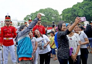Photo Caption: People takes a selfie with Presidential Security Details on Sunday (28/8), at the front yard of the Merdeka Palace, Jakarta (9/8)