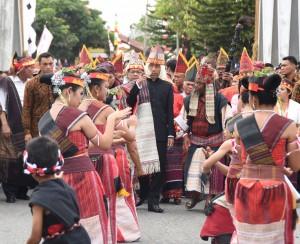 Presiden Jokowi disambut tarian adat saat akan membuka Karnaval Kemerdekaan Pesona Danau Toba, di Balige, Toba Samosir, Sumut, Minggu (21/8) sore. (Foto: Anggun/Humas)