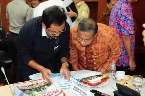 Gubernur Kepri Nurdin Basirun menunjukkan sebuah dokumen kepada Menko Perekonomian Darmin Nasution, di kantor Kemenko Perekonomian, Jakarta, Kamis (18/8) siang