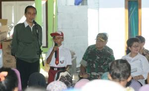 Presiden Jokowi menyaksikan seorang siswa SD menjawab pertanyaannya, saat membagikan PMT, di TPI Kapongan, Situbondo, Jatim, Rabu (14/9) siang. (Foto: Dina/Humas)