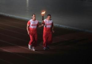 Atlet Ade Rai dan Anton Suseno membawa Obor Api PON XIX di GBLA, Jabar, Sabtu (17/9) malam. (Foto: Humas/Rahmat)