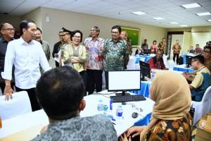 Presiden berbincang-bincang dengan petugas pelayanan amnesti pajak, di Kantor Pusat Ditjen Pajak, Jakarta, Jumat (30/9) malam. (Foto: BPMI/Laily)