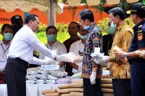 Kepala BNN Budi Waseso menunjukkan barang bukti narkoba yang akan dimusnahkan kepada Presiden Jokowi, di lapangan Silang Monas, Jakarta, Selasa (3/12) pagi. (Foto: AGUNG/Humas)