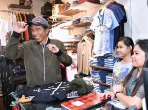 Presiden Jokowi mencoba sebuah topi saat blusukan ke Mega Mall, Manado, Senin (26/12) malam.