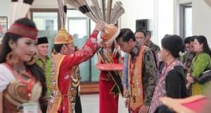 "Head of the Central Kalimantan's Dayak Customary Council (DAD, Agustiar Sabran, crowns President Jokowi as ""Raja Haring Hatungku Tungket Langit"", at Tjilik Riwut Airport in Palangkaraya, Central Kalimantan, Tuesday (20/12). (Photo by: Istimewa)"
