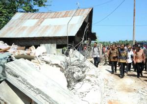 Presiden Jokowi meninjau rumah yang rusak terkena gempa, di Gampong Kuta Pangwa, Kecamatan Trienggadeng, Kabupaten Pidie Jaya, Kamis (15/12) siang. (Foto: Kris/Setpres)