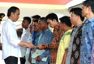 Presiden Jokowi menyerahkan simbolis sertifikat tanah program strategis kepada warga sejumlah daerah di Kalbar, di Kec. Entikong, Kab. Sanggau, Kalbar, Rabu (21/12) siang. (Foto: Laily/Setpres)