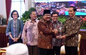 Presiden Jokowi menyerahkan penghargaan kepada Gubernur Jatim Soekarwo, di Istana Negara, Jakarta, Jumat (13/1) pagi. (Foto: JAY/Humas)