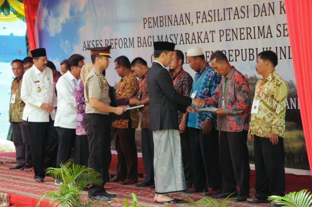 President Jokowi symbolically hands over 1,158 land certificates to the representatives of local residents, in Taman Raja Batu, Mandailing Natal, North Sumatra, on Saturday (25/3)