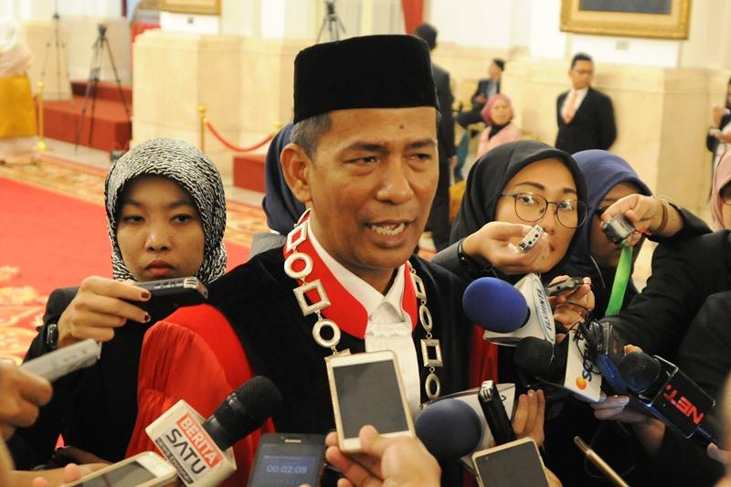 Hakim Mahkamah Konstitusi, Saldi Isra, menjawab pertanyaan wartawan usai pelantikan di Istana Negara, Jakarta, Selasa (11/4). (Foto: Humas/Deni).