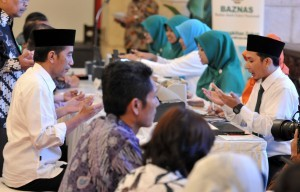 President Jokowi pays zakat to the BAZNAS employee at a counter at the State Palace, Jakarta, on Wednesday (14/6)