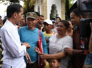 Presiden Jokowi menyapa warga yang turut antre dalam pembagian paket sembako di pelataran parkir Graha Saba Buana, Surakarta, Senin (26/6). (Foto: BPMI)