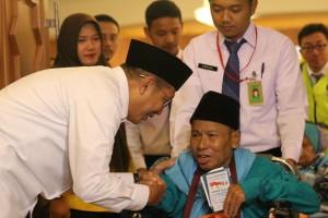 Menteri Agama Lukman Hakim Saefuddin menyalami salah seorang jemaah pada pelepasan kloter pertama jemaah haji Indonesia, di Embarkasi Pondok Gede, Jakarta. Jumat (28/7) Pagi