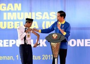 President Jokowi talks to a student who just has had measles-rubella (MR) vaccine shot at Sleman State Islamic Junior High School (Madrasah Tsanawiyah), Sinduharjo District, Ngaglik, Sleman Regency, Yogyakarta, on Tuesday (1/8)