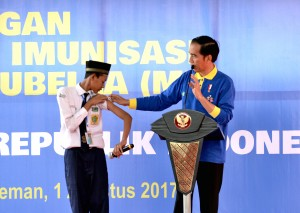 Presiden Jokowi berdialog dengan seorang siswa yang sudah memperoleh imunisasi MR, di Madrasah Tsanawiah Negeri 10 Sleman, Kelurahan Sinduharjo, Ngaglik, Kab. Sleman,  Yogyakarta, Selasa (1/8) pagi. (Foto: Agung/Humas)