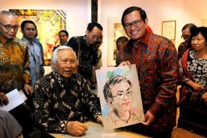 Seskab Pramono Anung mengangkut lukisan dirinya yang dibuat mendadak oleh Nyoman Gunarsa, di Bentara Budaya Palmerah, Jakarta Selatan, Senin (14/8) malam. (Foto: OJI/Humas)