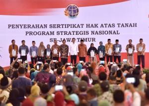 Presiden Jokowi saat menyerahkan sertifikat di New Sari Utama Convention Hall Mangli, Jember, Jawa Timur, Minggu (13/8)