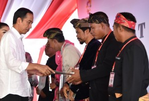 President Jokowi hands in land certificates to representatives of the people at at the field of Nurul Bilad Mosque in Mandalika Special Economic Zone (KEK) in Lombok Tengah Regency, West Nusa Tenggara province, Friday (20/10). (Photo by: Rahmad/Public Relations Division)