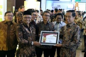 Presiden Jokowi menerima plakat dari Ketua KPK Agus Rahardjo saat meninjau pameran pada acara Pembukaan Konferensi Nasional Pemberantasan Korupsi Ke-12 serta Peluncuran Aplikasi e-LHKPN, di ruang Birawa Hotel Bidakara, Jakarta, Senin (11/12) pagi. (Foto: OZI/Humas)