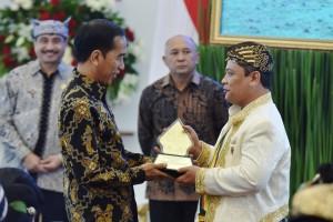 Presiden Jokowi menerima penghargaan saat  menerima audiensi Raja dan Sultan se-Indonesia di Istana Kepresidenan Bogor, Kamis, 4 Januari 2018.