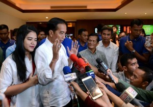 President Jokowi responds to reporters' questions after watching a movie titled 'Dilan 1990' in a cinema located in Senayan, Jakarta on Sunday (25/2)