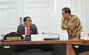 Presiden Jokowi menerima laporan dari Seskab Pramono Anung sebelum memimpin rapat terbatas, di Kantor Presiden, Jakarta, Selasa (20/2) siang. (Foto: JAY/Humas)
