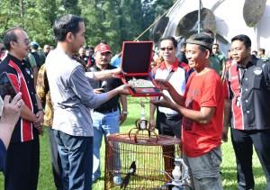 Presiden Jokowi menyerahkan hadiah kepada pemenang dalam acara Festival dan Pameran Burung Berkicau Piala Presiden Jokowi tahun 2018 di Kebun Raya Bogor, Minggu (11/3). (Foto: BPMI).