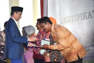 Presiden Jokowi saat menyerahkan sertifikat tanah di Function Hall, The Radiant Hotel, Desa Kondangsari, Kecamatan Beber, Kabupaten Cirebon, Minggu (11/3). (Foto: BPMI).